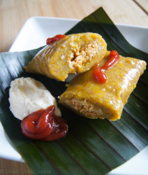 Pasteles en hoja served on a plate with a red and white sauce.