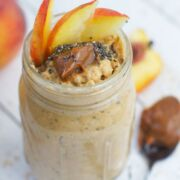 Peach and dulche de leche overnight oats in a glass jar.