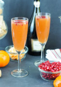 Two tangerine pomegranate mimosas served in flue glasses next to a bowl of pomegranate seeds.