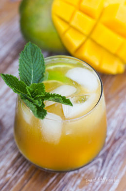 A mango mojito served in a glass with ice and a sprig of mint.