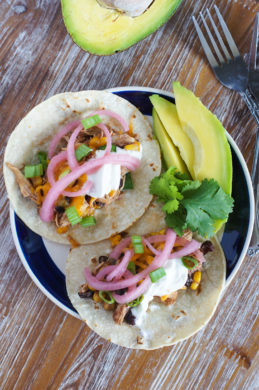 Two chicken chili tacos on a plate with sliced avocado.