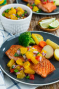 Pan seared salmon topped with peach salsa , served on a blue plate.