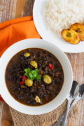 Black bean stew served in a white bowl next to a plate of white rice and fried plantain.