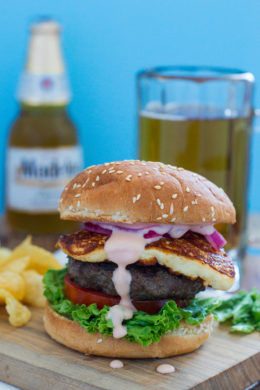 A queso frito burger in front of a glass of beer.