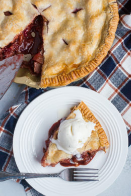 Apple and cranberry pie served with ice cream on a white plate.