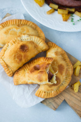 Ham and pineapple empanadas on a wooden serving board.