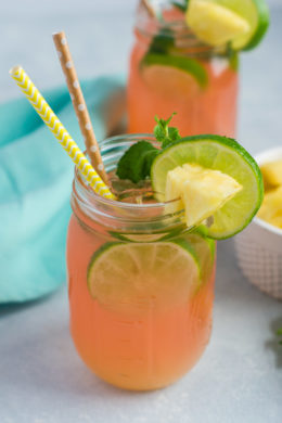 A cherry pineapple mojito in a glass mason jar with two straws and lime slice garnish.