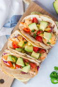 Three fish tacos topped with chunks of avocado.