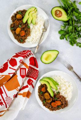 guiso de lentejas servido en dos platos con arroz y aguacate