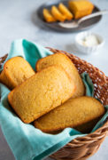 Four cornbread loaves in a basket with a blue cloth.