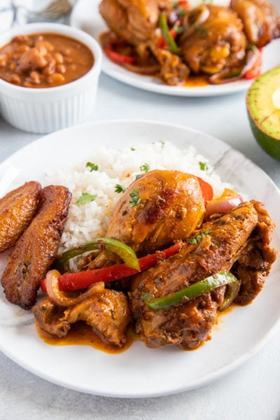 Pollo guisado served on a white plate with rice and garnished with fresh herbs.