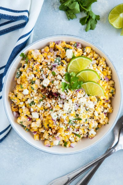 Esquites served in a white bowl with slices of lime and topped with fresh cilantro.