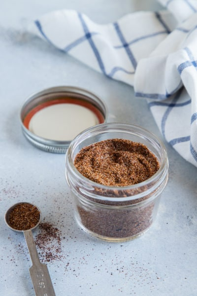 Homemade taco seasoning in a glass jar next to a blue and white cloth.