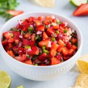 Fresh strawberry salsa in a white bowl next to tortilla chips.