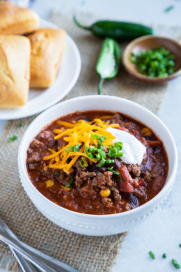 Chili served in a white bowl with sour cream, shredded cheese and sliced green onions.