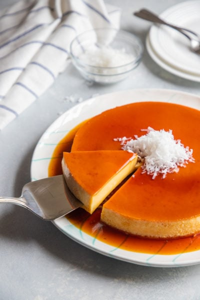 A slice of coconut flan being lifted up on a cake slice.