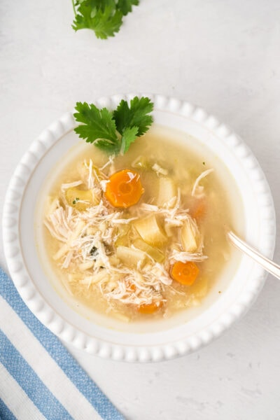 Chicken noodle soup served in a white bowl with fresh cilantro.