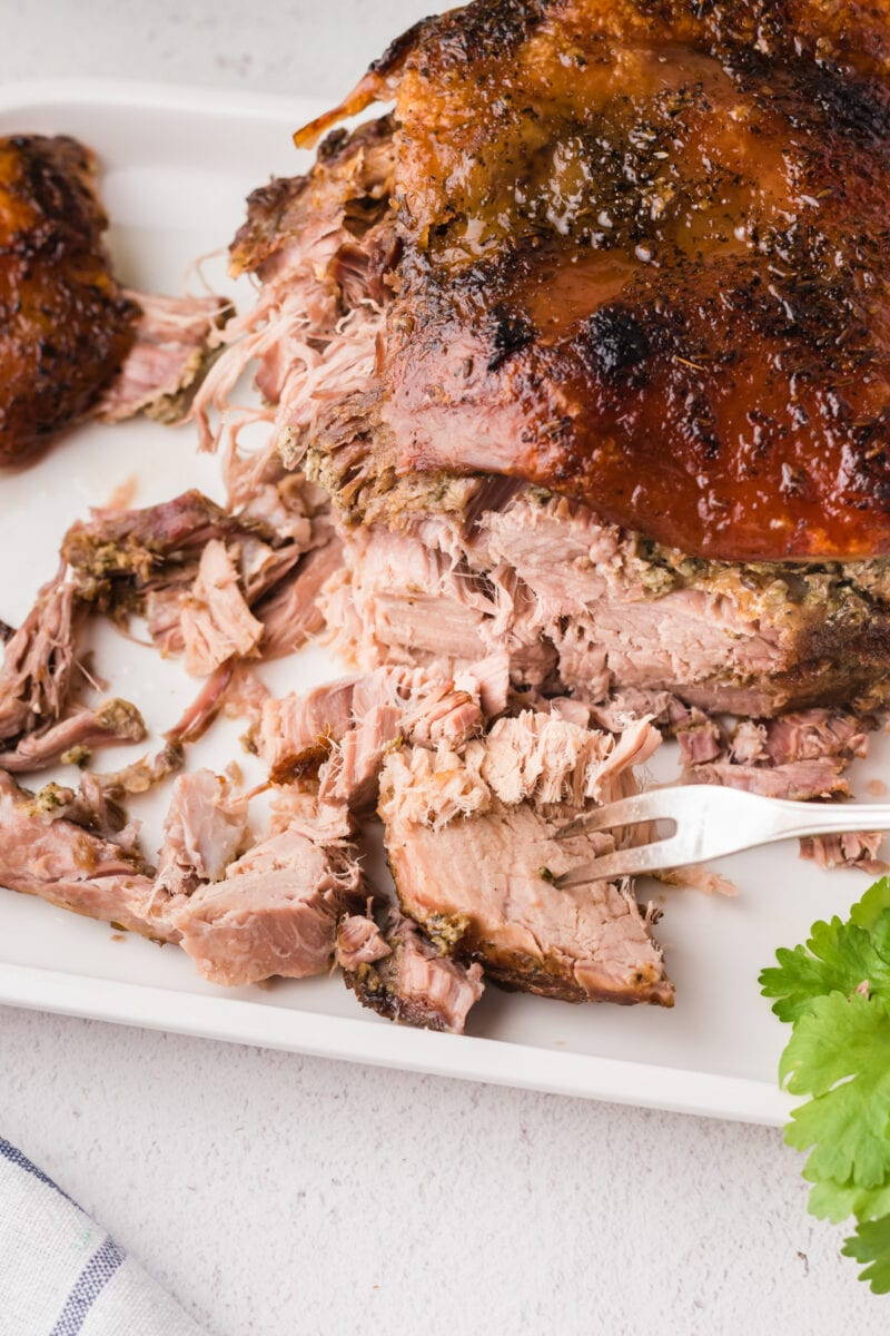 Pork roast cut into slices on a white plate and a fork in one piece.